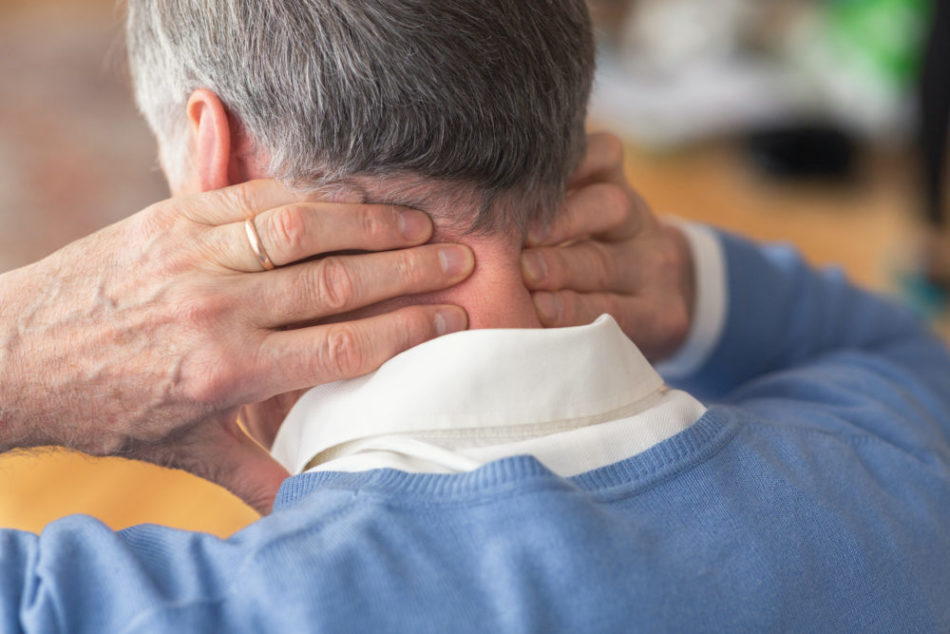 elderly man holding the back of his neck due to pain