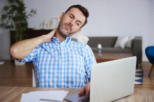 middle aged man rubbing his neck due to looking down at his laptop to long