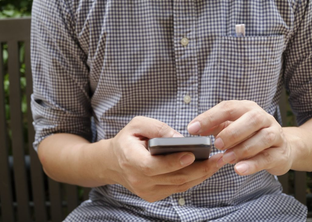 young male texting on his phone