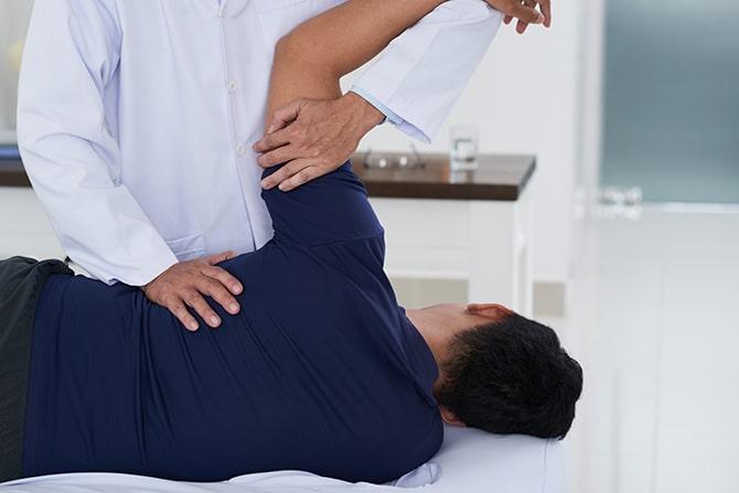chiropractor examining male patients shoulder