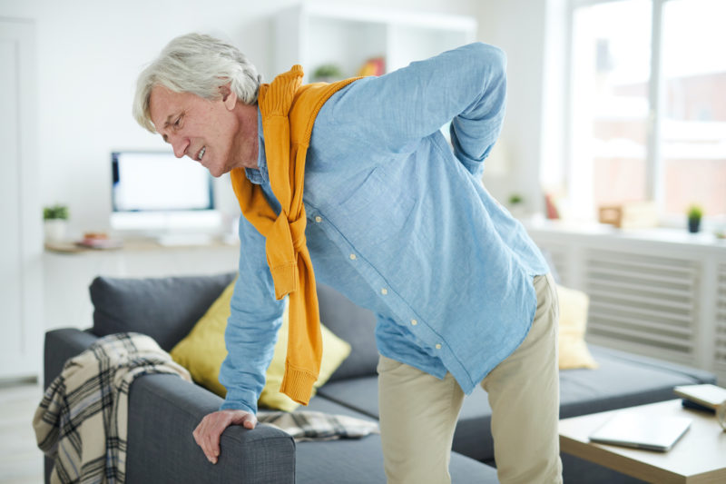 elderly person holding their back due to pain