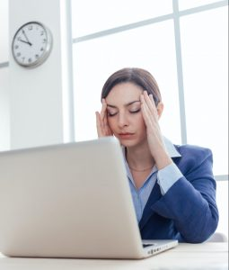 business woman holding her head due to a headache