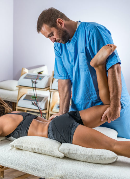 therapist stretching patients knee and hip