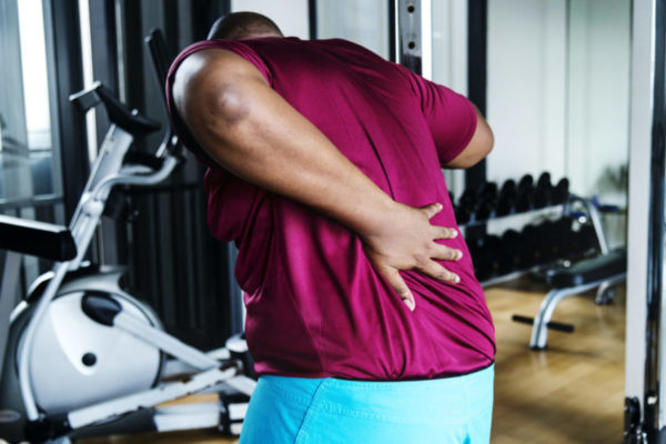 young man hiolding his lower back due to a workout injury