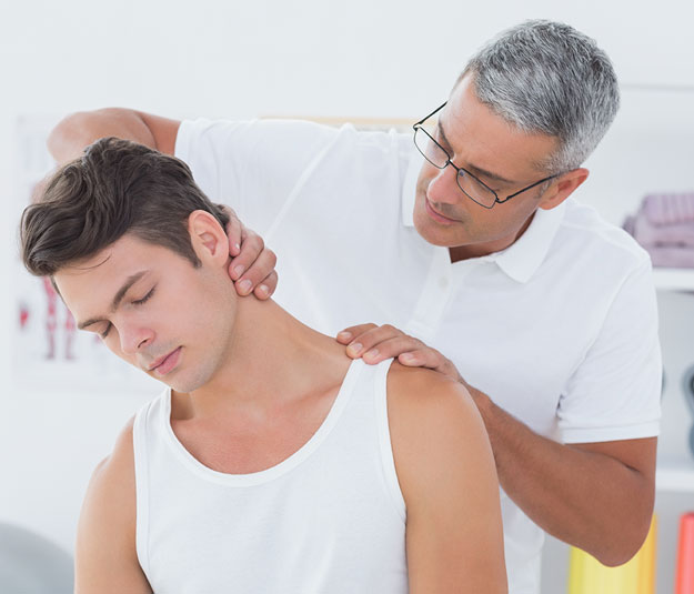 chiropractor examining male patients neck