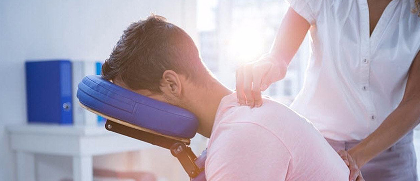 chiropractor examining patients neck and upper back