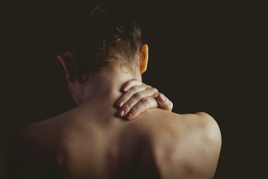 woman holding the back of her neck due too pain