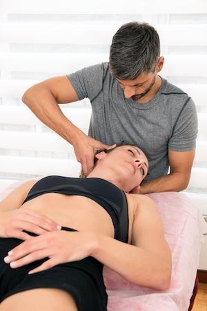 chiropractor adjusting female patients neck