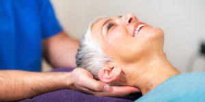 chiropractor holding a femal patients head
