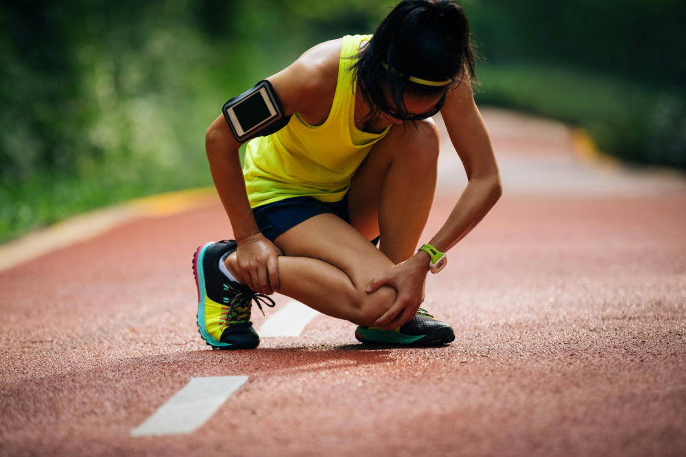 young woman holding her knee and ankle due to a running injury